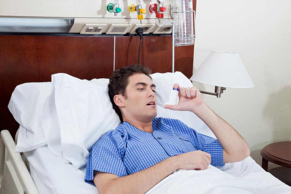 Мужчина в постели с ингалятором
